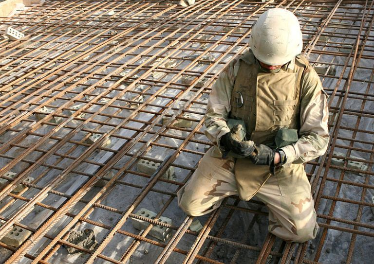 Fallujah, Iraq. Steelworker 3rd Class Robert Sprague ties together rebar before a concrete placement on a bridge project.